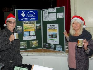 Lorraine and Rose stood in front of a project display board.
